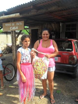A leitora Zilá entrega a Sacola de Leitura para a família da Dona Cândida Farias.