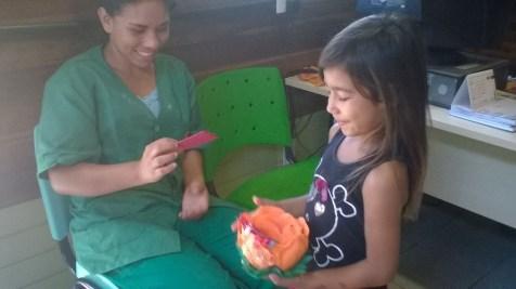 A pequena Diully distribuindo poemas às mulheres do CRAS Ilhas.