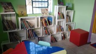Novo espaço para os livros infantis com estante construida com caixas de frutas.