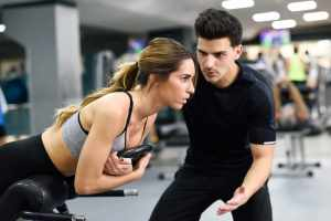 student being coached by personal trainer