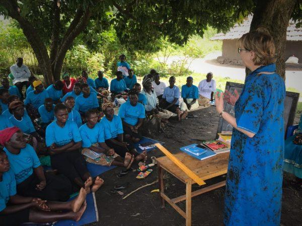 Karon standing, speaking to group of seated Ugandan women outdoors.