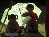 A small boy and girl shelter from the sun under an umbrella on the grass. They have an uneaten burger next to them and are playing with folded white paper