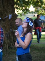 A woman with long brown hair wearing a head dress of large blue flowers smokes a cigarette. She is standing next to a tree on which leaflets are pinned to a string