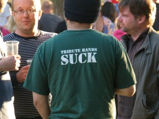 """Close up of a man wearing a green t shirt that reads """"Tribute bands suck"""""""