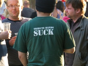 "Close up of a man wearing a green t shirt that reads ""Tribute bands suck"""