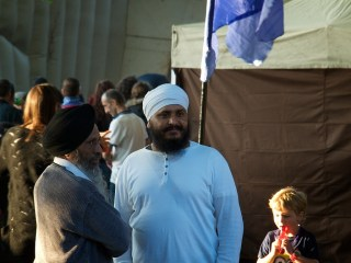 Two men with beards and turbans stand in the dusk by a gazebo. Behind them a small boy eats a lollipop
