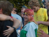 A woman with orange and pink hair and a flowery headband smiles at two people hugging