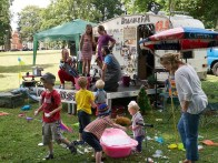 "Children play in front of the ""Bramble FM"" stage in the kids area, which is made from a caravan. Two grown ups in party hats speak into microphones on the small stage"