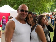 A man and woman in white vests embrace and smile into the camera