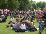 A crowd of festival goers on the grass by the main stage. Some stand, some sit on picnic blankets and there are trees in the background