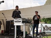 A DJ plays a tune from his laptop on the main stage. He wears white headphones around his neck. The stage manager stands behind at the back of the stage