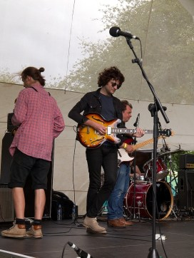 A guitarist on the main stage tunes between songs, He stands with his legs crossed while other band members adjust their instruments behind