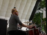 A drummer with yellow-rimmed sunglasses plays a shiny red drum kit on the main stage. His sticks are moving so fast that they appear blurred
