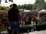 A shot of the main stage crowd, taken from behind a singer as he rests between verses. Food stalls and trees in the background. The sun is shining