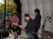 A guitarist, bass player and saxophonist seen from behind on the main stage as they play to a happy crowd