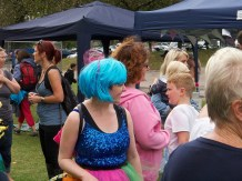 A woman in an electric blue wig and blue sequinned top is smiling away from the camera towards a crowd of people. She is carrying a hula hoop