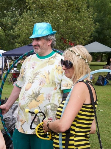 A man and woman hold hula hoops and smile. She is dressed as a bee and has glitter on her face. He wears a shint blue trilby hat and a t shirt decorated with pineapples