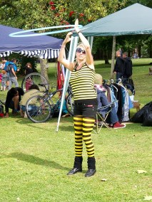 A blonde woman wearing ywllow and black striped t shirt and tights twirls a hula hoop so fast that it appears blurred