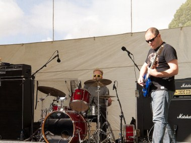 A guitarist and drummer surrounded by large amps on the main stage. They are both men and wearing t shirts and sunglasses