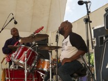 Close up of Dub from Atlantis drummer, with bassist in the background. They are waiting for a song to start.