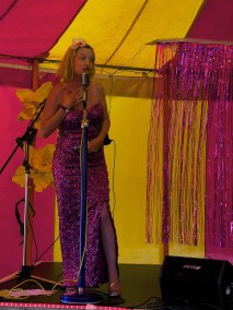 A woman in a pink sequinned gown sings into an old-fashioned microphone in the cabaret tent. Behind her are giant flowers and a glitter curtain