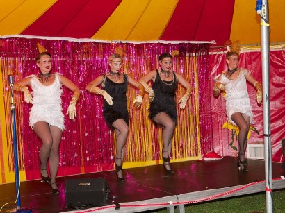 Four can can dancers in fringed dresses, golden gloves and feathered hair bands. They are on stage in the cabaret tent and there is a pink glittery curtain behind them
