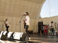 The 45s play on the main stage. The singer and guitarist is in the foreground with bassist and drummer behind. They are all wearing sunglasses, and matching shirts and ties