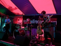A band prepares to play on the market stage. There is a guitarist, bassist and drummer and they are all bathed in pink light coming through the canvas roof