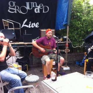 A band play in the garden of the Grounded cafe. A man plays an acoustic guitar while sitting on a cahon and singing. His bandmate is blowing a harmonica.