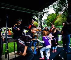 Children with their faces painted dance to a band on a small stage