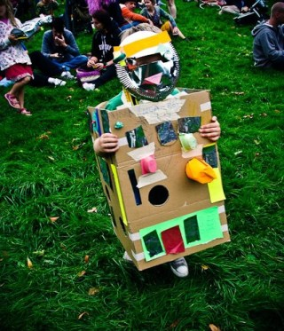 A child in a robot costume made from a cardboard box decorated with squares of coloured paper and foil. The mask is a shiny round plate with a slot for eyes and coloured stickers.