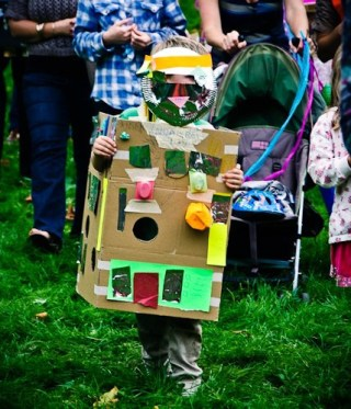 A boy in a robot costume decorated with coloured paper, sticky tape and yoghurt pots stands on the grass.