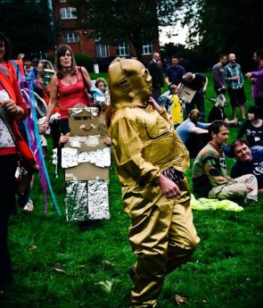 A woman dressed as C3PO from Star Wars walks past the camera. In the background is a child in a robot costume decorated with tinfoil, and a crowd of adults enjoying the festival