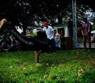 A breakdancer balances on his hands on the grass, his body almost parallel to the ground. Two other young men are watching and cheering him on.