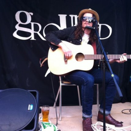 A man with big sunglasses and long hair sits in the Grounded cafe garden and plays a large acoustic guitar. He has a harmonica around his neck