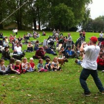 A man entertains the crowd on the grass, his t shirt billowing as he moves. At the front of the crowd is a row of small children, adults are behind.