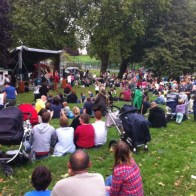 A crowd of people sit on the grass and watch the show. There are many families. Behind are trees and tennis courts.