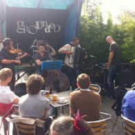 A band entertain drinkers in the Grounded cafe bar garden. There is an accordion, a double bass and a fiddle