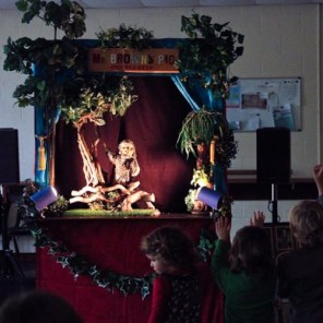 Children wave at the puppet show Mr Brown's Pig. The small raised stage is decorated with leaves and pieces of wood, and there is a puppet on stage waving back at the children