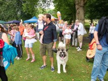 Revellers enjoy the show amid the trees and market stalls. A family with two small girls and a very large dog are in the foreground.