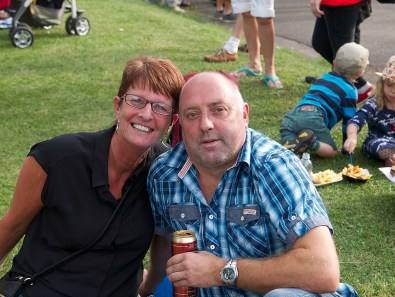A man and a woman sit on the grass and smile at the camera while enjoying a can of cider.