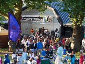 The inflatable main stage in late afternoon, framed by large trees. The crowd are milling as they wait for the next band to come on
