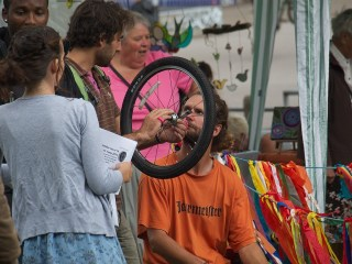 A man holding a small bicycle wheel explains something to another man sitting at a market stall