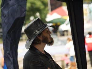 Side view of a bearded chap with a black leather hat, looking pensively out from a gazebo