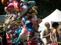A man walks from left to right with a toddler on his shoulders. Behind them a woman holds an enormous bunch of colourful balloons