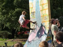 A young man does a trick on a vertical skateboard ramp while others watch