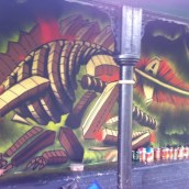 A nearly finished mural showing a dinosaur made from rows of houses. Many paint cans sit on the wall alongside