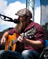 A man with a bushy beard is playing an accoustic guitar and singing with his eyes closed.
