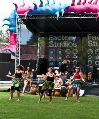 Six female dancers perform on the grass in front of the main stage. They wear brightly printed skirts and headscarves. Behind them are a row of four men drumming and singing. The stage behind is decorated with an enormous pink and blue inflatable shaped like a spikey snake.