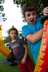 Two boys brandish inflatable swords towards the camera